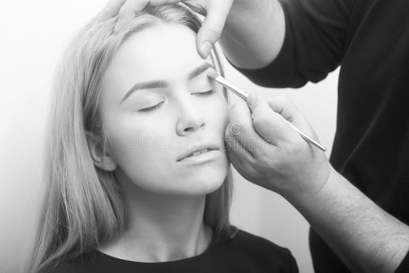 Manos que aplican lápiz corrector en los párpados de la muchacha con el cepillo del maquillaje fotografía de archivo