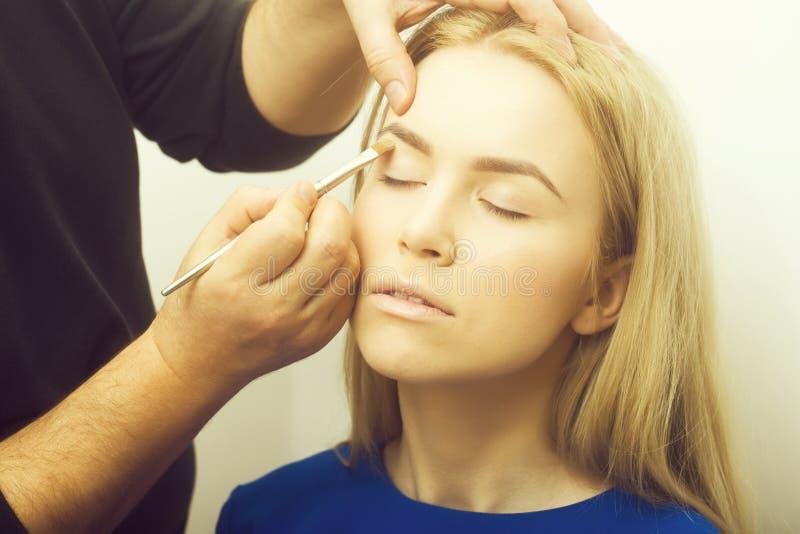 Manos que aplican lápiz corrector en los párpados de la muchacha con el cepillo del maquillaje fotografía de archivo libre de regalías