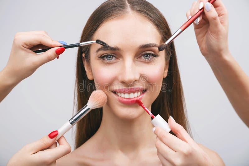 Manos que aplican maquillaje fotos de archivo
