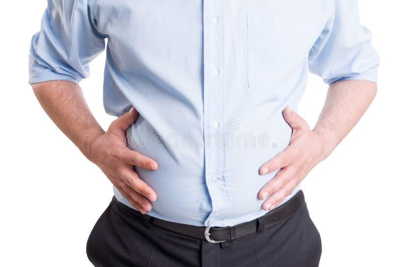 Manos que asen el abdomen hinchado foto de archivo