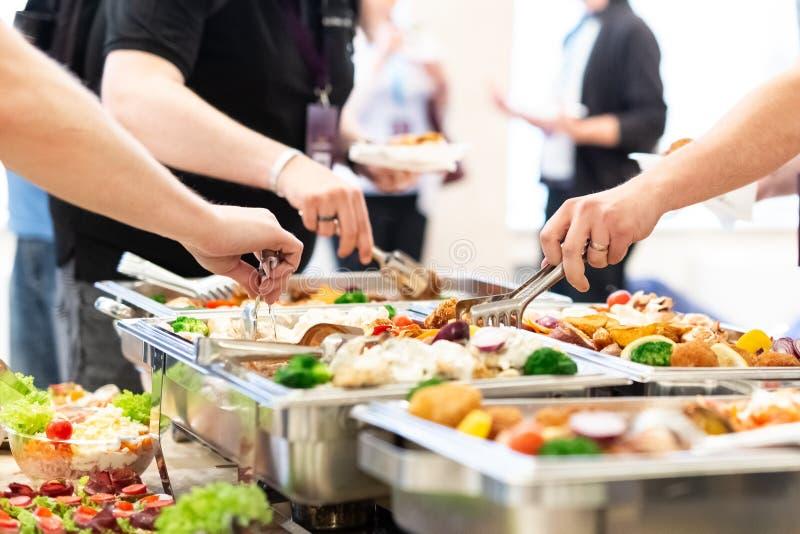 Manos que cogen la comida de la tabla del abastecimiento del buffet en la fiesta foto de archivo libre de regalías