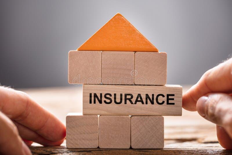Manos que construyen la casa With Insurance Block modelo imagenes de archivo