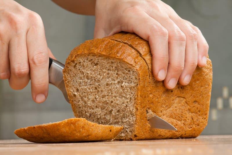 Manos que cortan el pan de centeno imagen de archivo