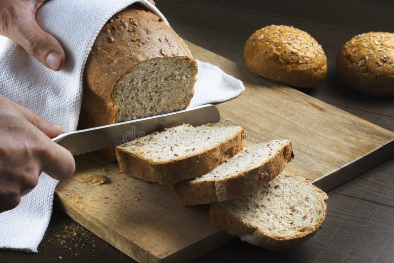 Manos que cortan el pan hecho en casa fresco en una tabla fotos de archivo libres de regalías