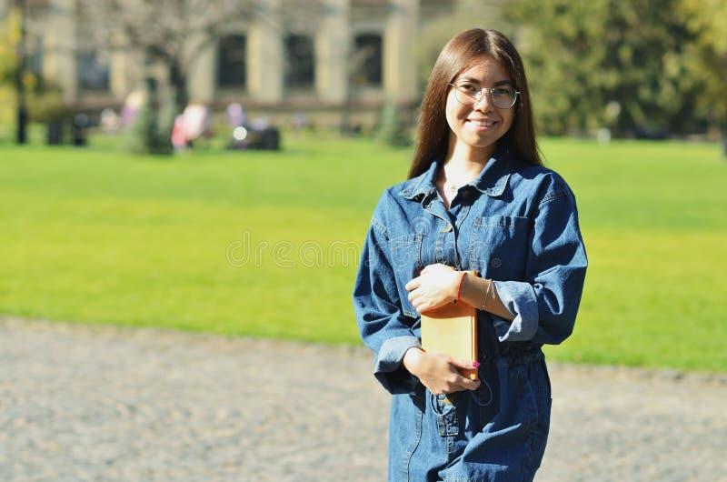 Manos que cruzan de la mujer bonita acertada feliz y sonrisa cerca de campus imagen de archivo libre de regalías