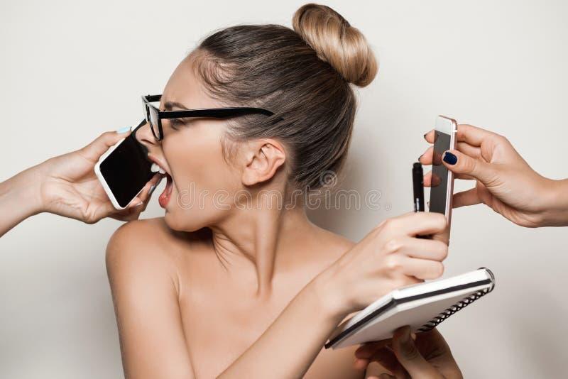 Manos que dan los teléfonos a la empresaria desnuda hermosa joven que sostiene el cuaderno fotos de archivo