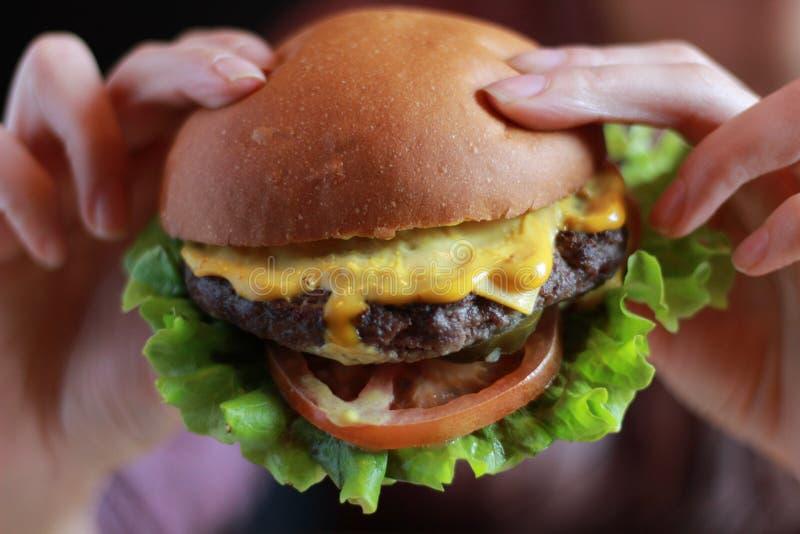 Manos que detienen el primero plano de la hamburguesa, cierre fotos de archivo