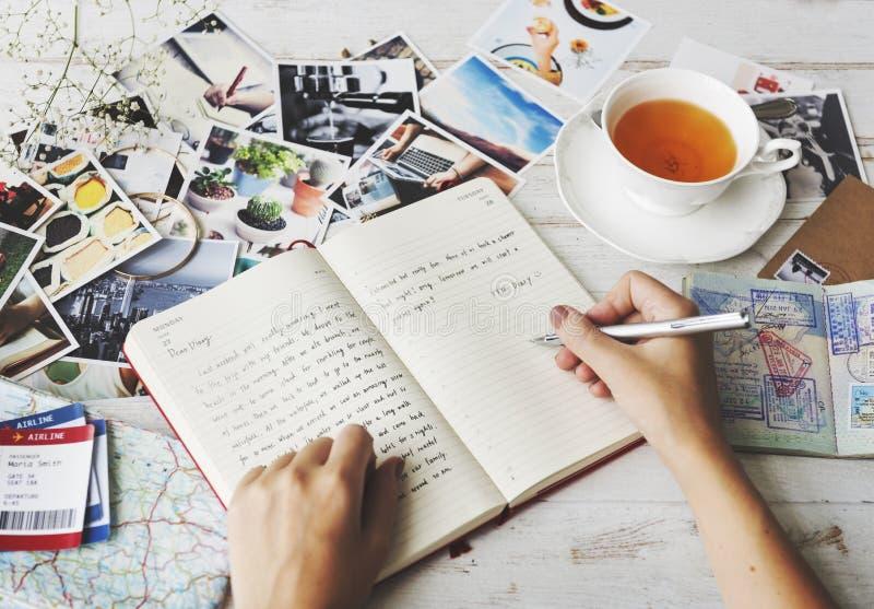 Manos que escriben concepto del té del diario del viaje fotos de archivo