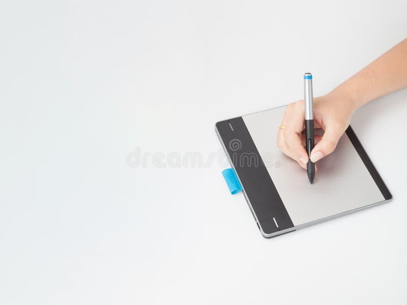 Manos que escriben en la tableta digital imagen de archivo libre de regalías