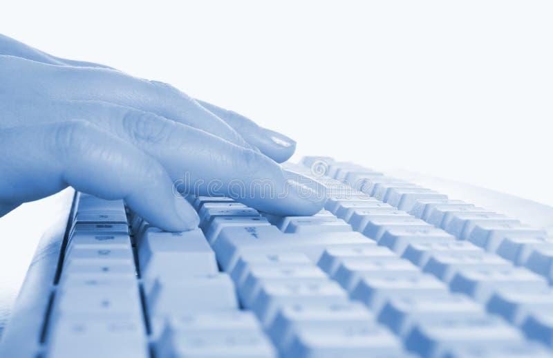 Manos que escriben en un teclado de ordenador foto de archivo