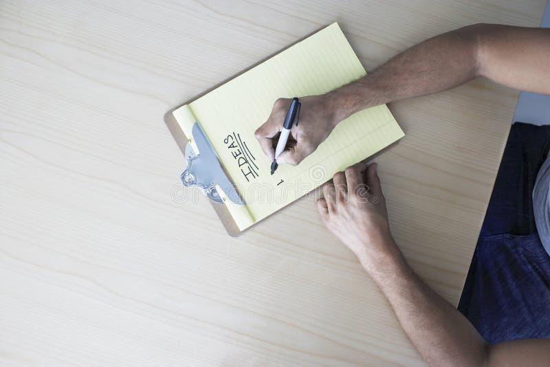 Manos que escriben 'ideas' en el tablero fotografía de archivo