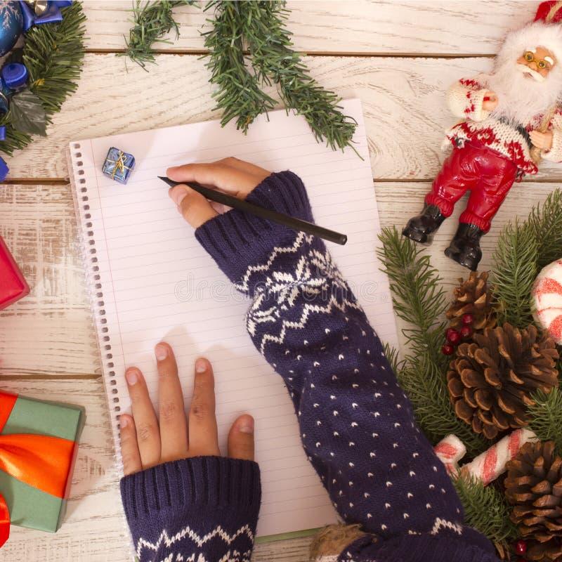 Manos que escriben la letra a Santa Claus en la harina de madera cerca cajas del regalo de la Navidad de las actuales imagenes de archivo