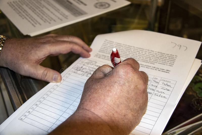 Manos que firman la petición para que marijuana recreativa sea puesta en la votación en noviembre de 2018 fotos de archivo