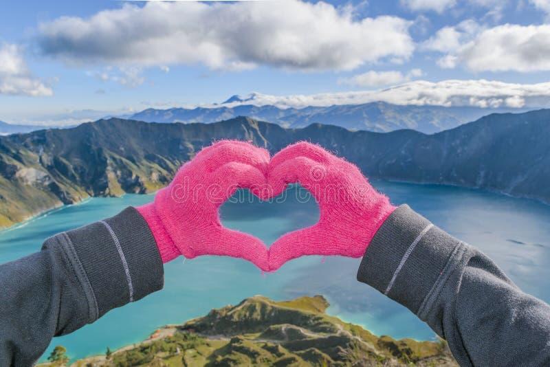 Manos que forman forma del corazón en el lago Quilotoa, Latacunga, Ecuador imagenes de archivo