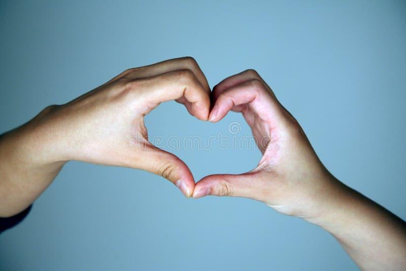 Manos que hacen dimensión de una variable del corazón fotos de archivo libres de regalías