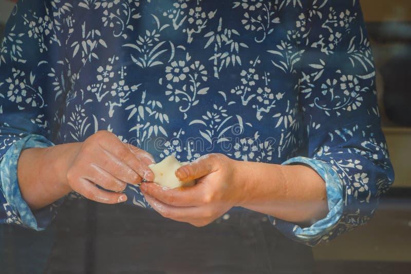 Manos que hacen el bollo cocido al vapor chino foto de archivo