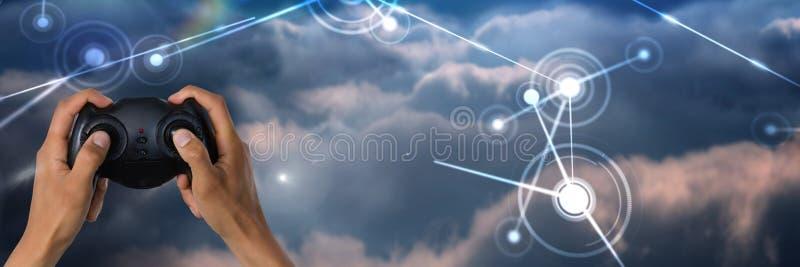 Manos que juegan con el regulador del juego de ordenador con las conexiones ligeras brillantes en fondo del cielo foto de archivo libre de regalías