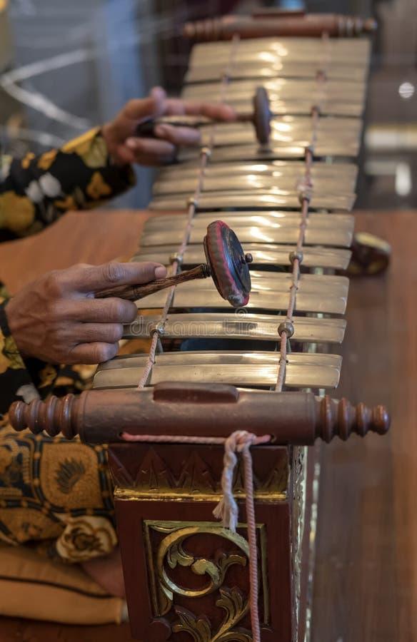 Manos que juegan el slenthem, un instrumento de música tradicional Javanese imagen de archivo