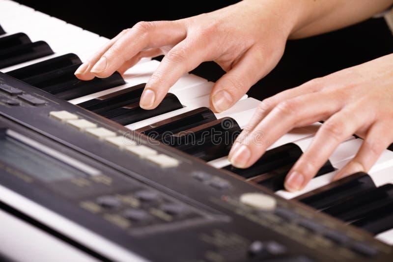 Manos que juegan música en el piano imagen de archivo