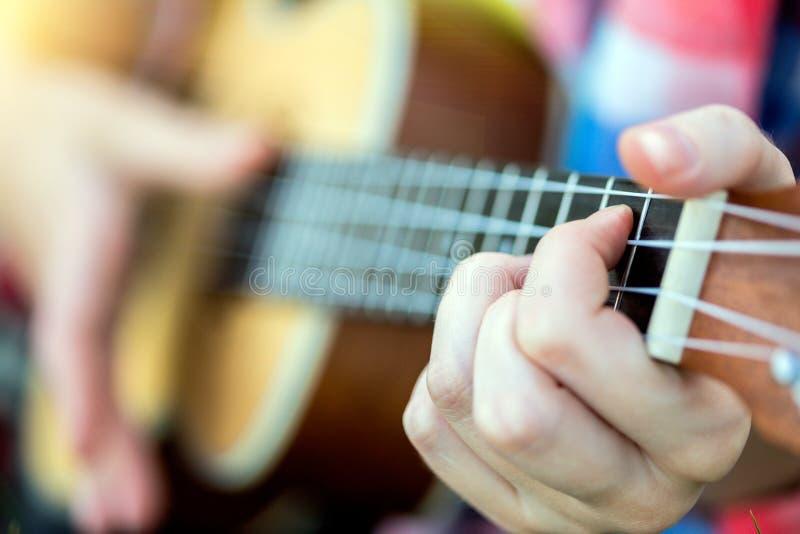 Manos que juegan un primer de la guitarra fotos de archivo