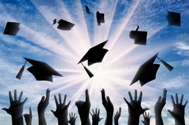 Manos que lanzan el casquillo graduado en cielo imagenes de archivo
