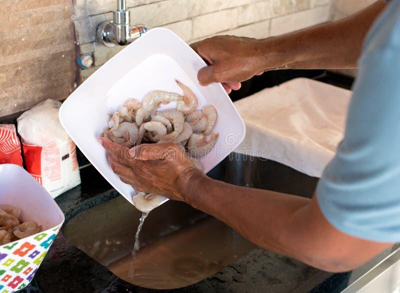 Manos que limpian el camarón crudo fotos de archivo libres de regalías