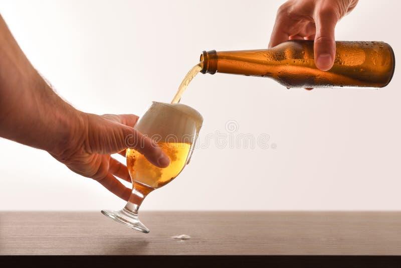 Manos que llenan un vidrio de cerveza en blanco aislado tabla de madera imágenes de archivo libres de regalías