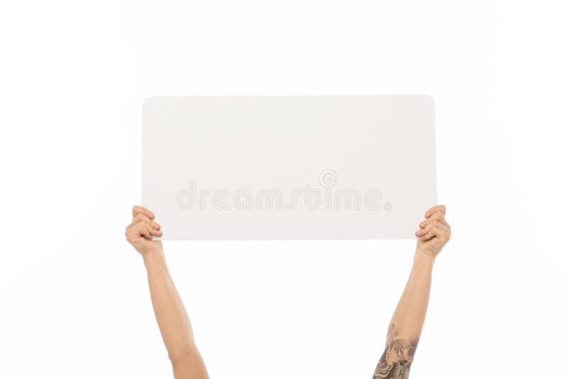 Manos que llevan a cabo al tablero blanco en blanco fotografía de archivo