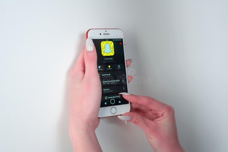 Manos que llevan a cabo el color de Apple Iphone 8 con el app de Snapchat en la pantalla fotos de archivo libres de regalías