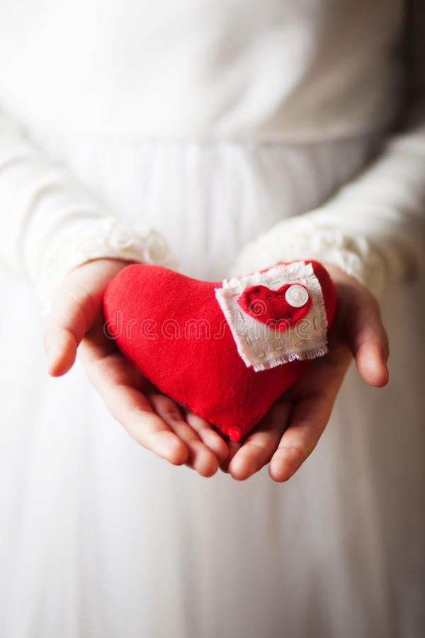 Manos que llevan a cabo el corazón rojo de la materia textil foto de archivo