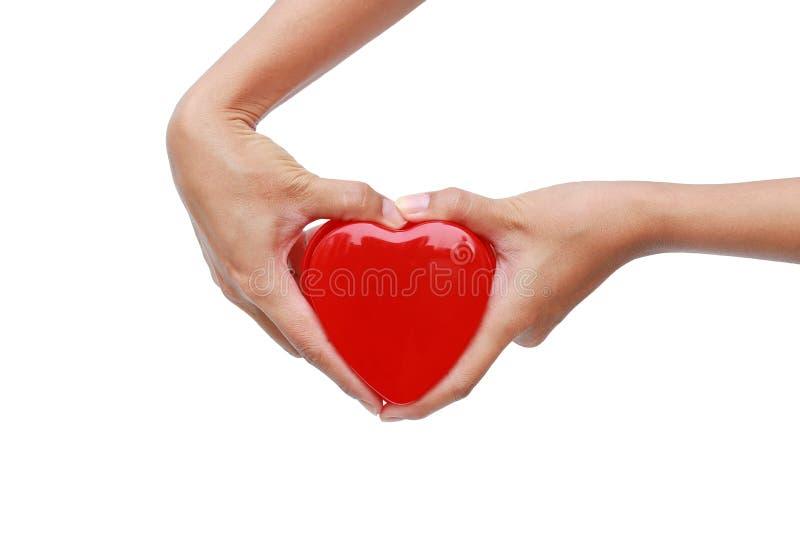 Manos que llevan a cabo el pequeño corazón del regalo el día de tarjeta del día de San Valentín aislado en el fondo blanco fotografía de archivo libre de regalías