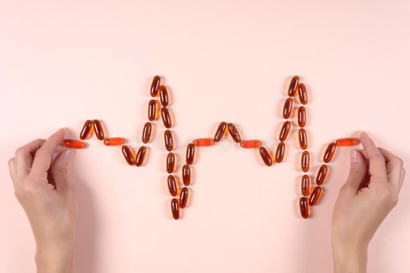 Manos que llevan a cabo latido del corazón de cápsulas de la lecitina Atención sanitaria o concepto sano del corazón Visión super imagen de archivo libre de regalías