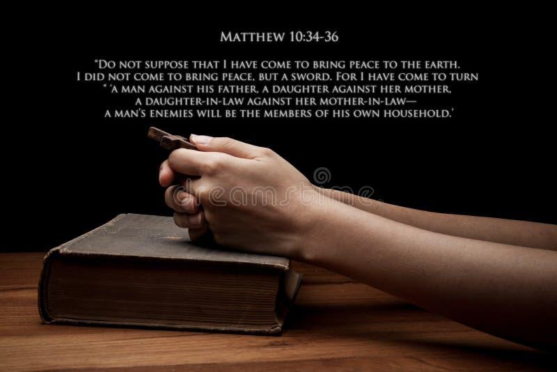 Manos que llevan a cabo una cruz en la Sagrada Biblia con verso imagenes de archivo