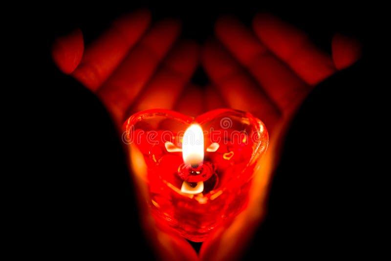 Manos que llevan a cabo una vela ardiente de la forma del corazón imagen de archivo
