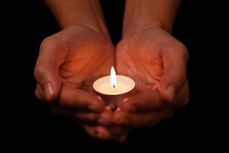 Manos que llevan a cabo y que protegen luz de una vela encendida o ardiendo de la vela en oscuridad imagen de archivo libre de regalías