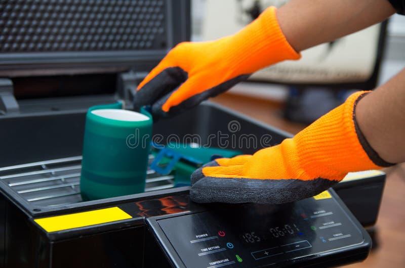Manos que llevan los guantes anaranjados que trabajan en la impresión negra imagen de archivo libre de regalías