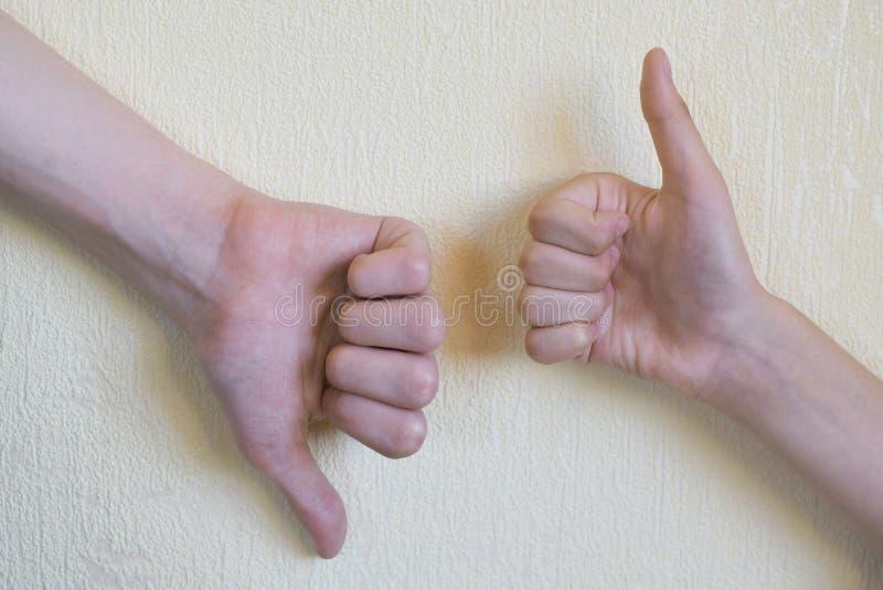 Manos que muestran el pulgar para arriba y el pulgar abajo imagenes de archivo