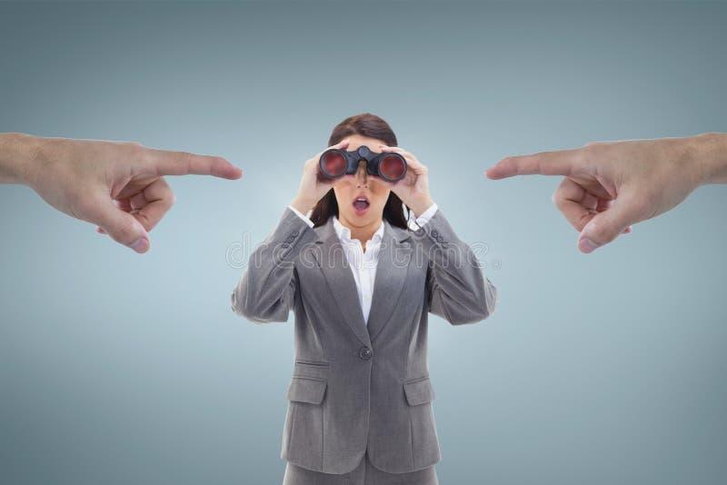 Manos que señalan en la mujer de negocios emocionada que mira a través de los prismáticos contra fondo azul imagenes de archivo