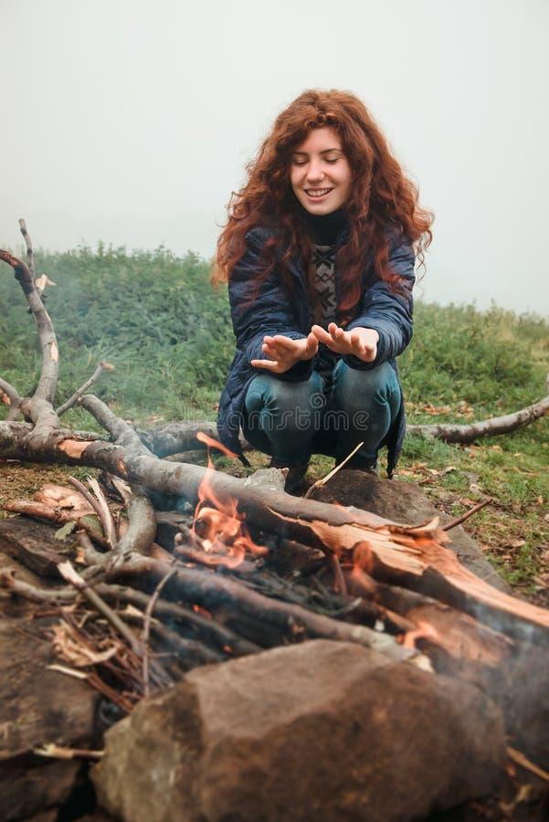 Manos que se calientan de la muchacha pelirroja cerca del fuego fotografía de archivo