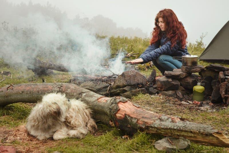 Manos que se calientan de la muchacha pelirroja cerca del fuego al aire libre imagenes de archivo