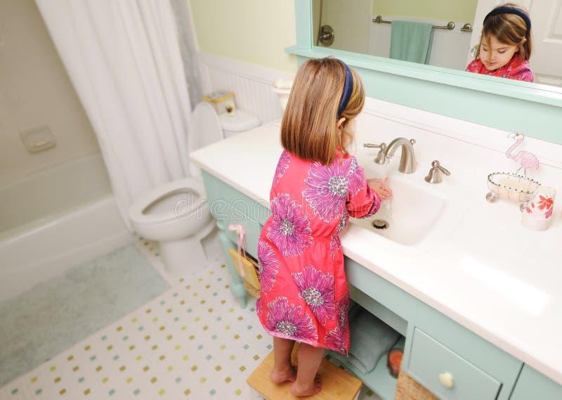 Manos que se lavan de la chica joven en cuarto de baño imagenes de archivo
