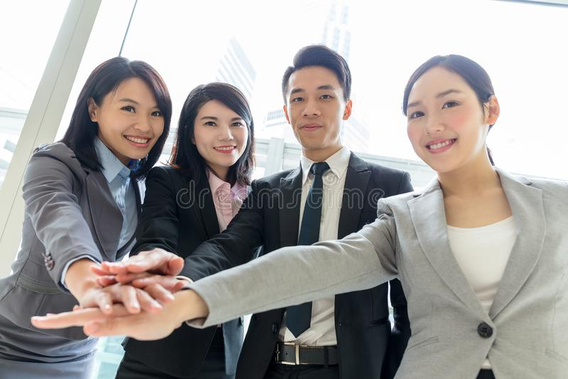 Manos que se unen a del equipo asiático del negocio antes de trabajar foto de archivo libre de regalías
