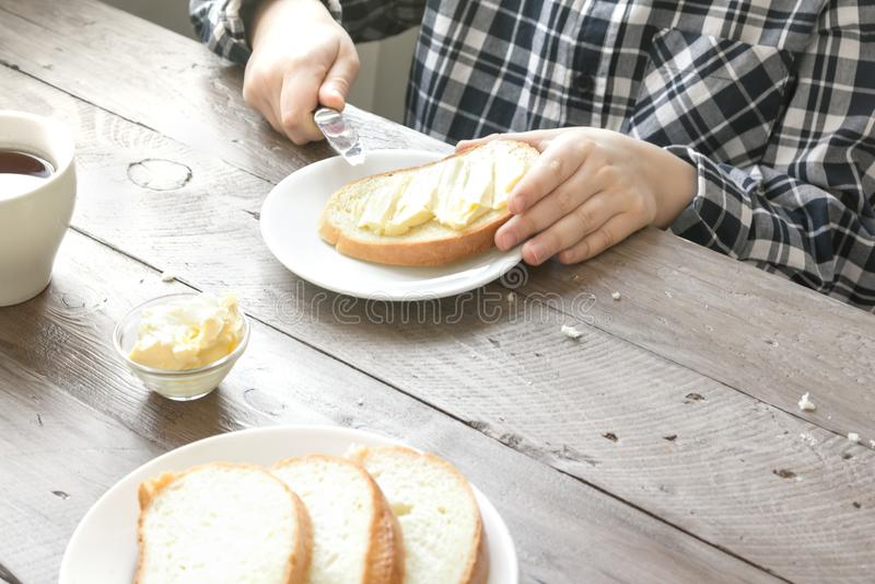 Manos que separan la mantequilla en el pan foto de archivo libre de regalías