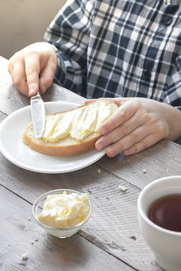 Manos que separan la mantequilla en el pan fotos de archivo libres de regalías