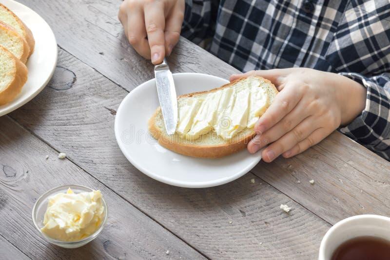 Manos que separan la mantequilla en el pan imagenes de archivo