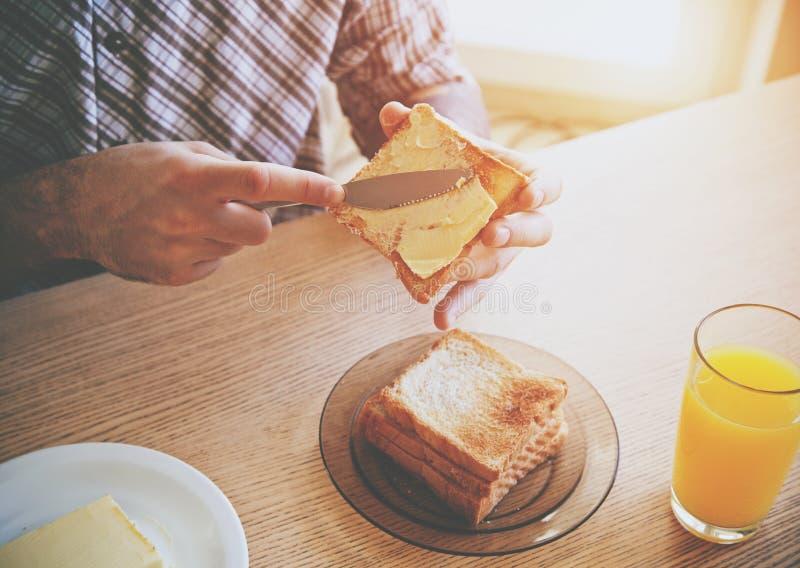 Manos que separan la mantequilla en el pan tostado fotos de archivo libres de regalías