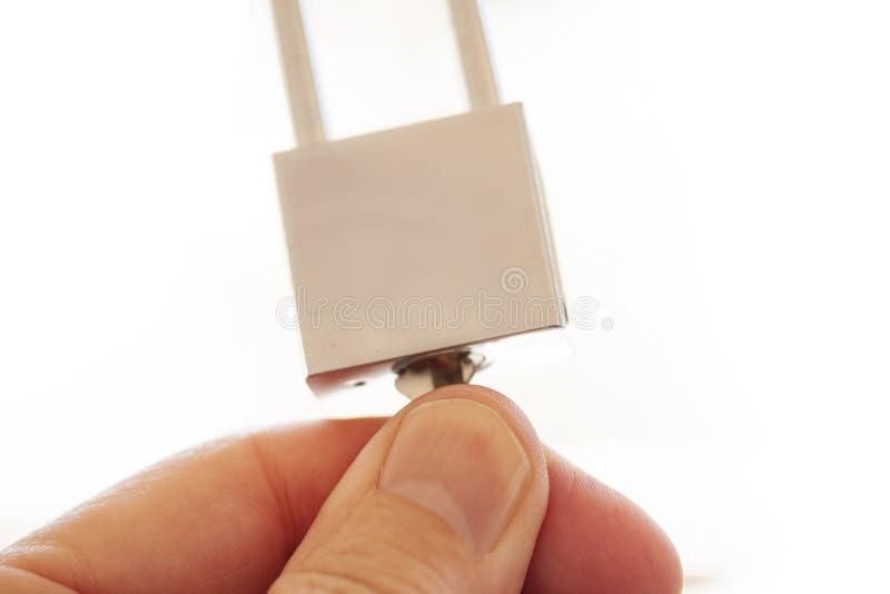 Manos que sostienen, cerrando y desbloqueando el candado de acero inoxidable aislado sobre el fondo blanco imagen de archivo