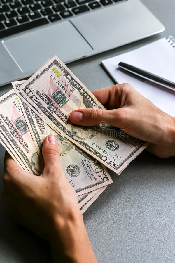 Manos que sostienen cientos y cincuenta billetes de banco del dólar imagen de archivo