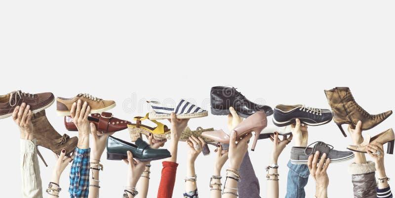 Manos que sostienen diversos zapatos en fondo aislado fotos de archivo