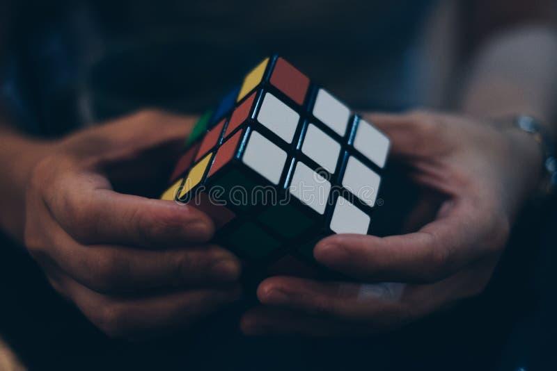 Manos que sostienen el cubo del ` s de Rubik imagen de archivo libre de regalías